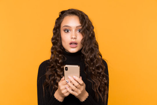 Scared and surprised woman holding phone isolated