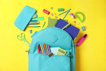 Stylish backpack with different school stationery on yellow background, flat lay