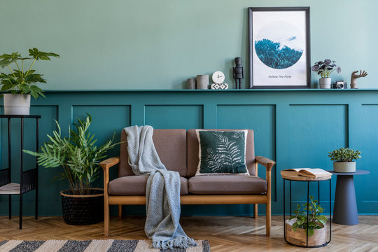 Stylish interior design of living room at apartment with brown sofa, a lot of plants, design furnitures and elegant accessories. Mock up poster frames on the shelf. Green wood panelling. Home staging.