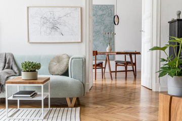 Obraz Stylish scandinavian living room with design mint sofa, furnitures, mock up poster map, plants and elegant personal accessories. Modern home decor. Open space with dining room. Template Ready to use.  - fototapety do salonu