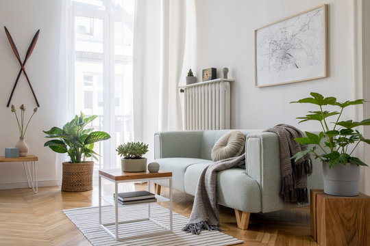 Stylish scandinavian living room with design mint sofa, furnitures, mock up poster map, plants and elegant personal accessories. Modern home decor. Bright and sunny room. Template Ready to use.