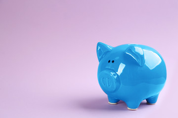 Blue piggy bank on violet background. Space for text