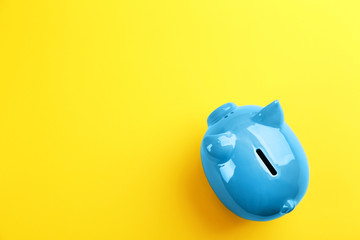 Blue piggy bank on yellow background, top view. Space for text