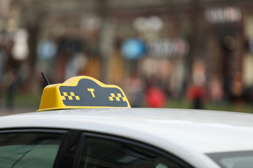Taxi cab with yellow sign on city street, closeup