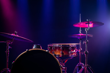 Drums and drum set. Beautiful blue and red background, with rays of light. Beautiful special effects of smoke and lighting. Musical instrument. Close-up photo.