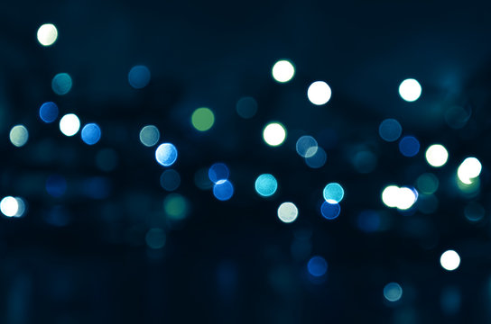 Dark blue background with blue and green bokeh lights