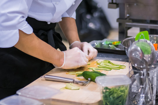 Chef hands peels and slices fresh green cucumber, pickle with scraper, knife at cuisine of restaurant. Professional cooking, catering, culinary, gastronomy and food concept