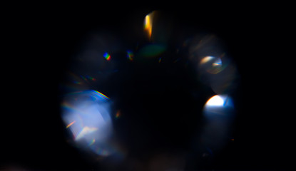 Lens Flare, Abstract Bokeh Lights. Leaking Reflection of a Glass, Crystal, Defocused Shining Colorful rainbow Light Leaks, Rays on Black Background