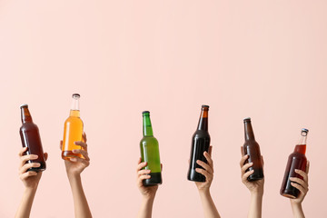 Fotorolgordijn Bar Hands with bottles of beer on color background