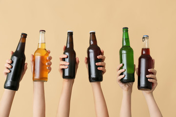 Poster Alcohol Hands with bottles of beer on color background