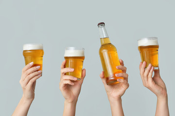 Hands with fresh beer on grey background