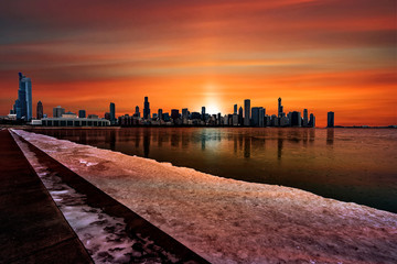 Chicago's city skyline silhouette against a deep orange sunset reflecting off the frozen Lake Michigan in Illinois, USA.