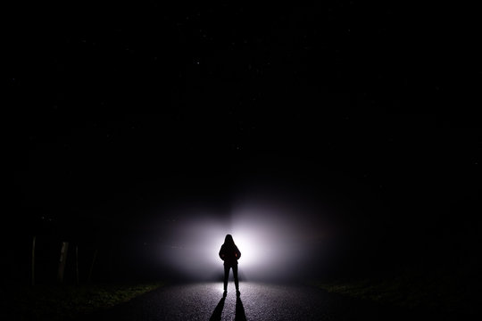 Silhouette of a woman in the darkness. Night Photography. Bright light shining behind dark mysterious figure. Ghostly, mystical, surreal person standing.