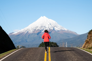 Woman runs on a straight road toward snow mountain. Running outdoors concept. Achieve goal, motivation and determination concept.