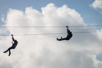 People having fun using a zip line