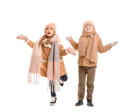 Little children in winter clothes on white background