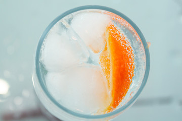 glass with oranges, ice, sparkling water close-up