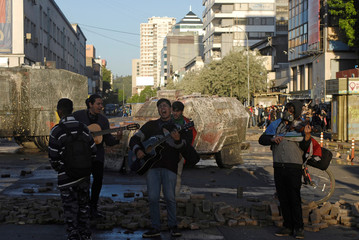 Locals play musical instruments in front of riot police vehicles during a protest against Chile's government in Concepcion