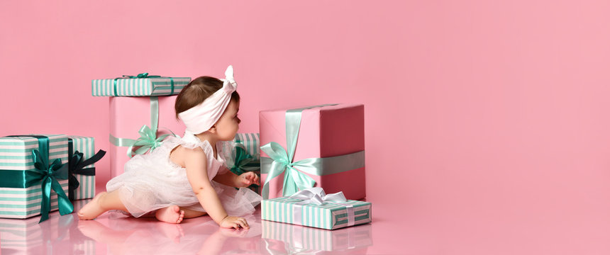 Little baby girl sits surrounded by gift boxes on a pink background