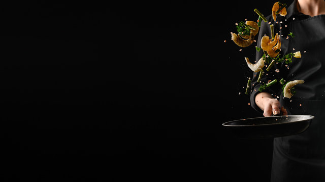 Seafood, frying shrimp with vegetables, a chef on a black background. Advertising banner for the sale of seafood, on a black background for design