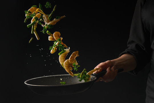 Thai cuisine, the chef cooks shrimps with lemon, frying in a pan. Freezing in motion, on a black background. Advertising photo, seafood sale.