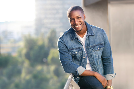 Relaxed and casual modern african american male portrait in blue jean jacket on a city rooftop during sunset