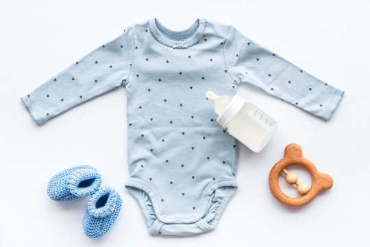 Newborn baby boy set - blue clothes as bodysuit, booties, toys - on white table top-down