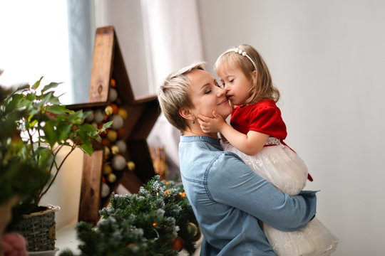 Child with disabilities with mom, Christmas tree