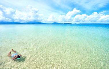 Black woman in bikini snorkeling in crystal clear water in El Nido - Palawan - Philippines