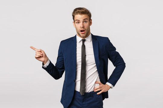 Surprised, speechless young businessman with blond hair, bristle, wearing classic suit, starting career new company, asking question about coworker, pointing left and look amused, white background