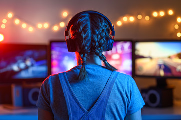 Gamer or streamer girl at home in a dark room playing video games with friends online. A young man...