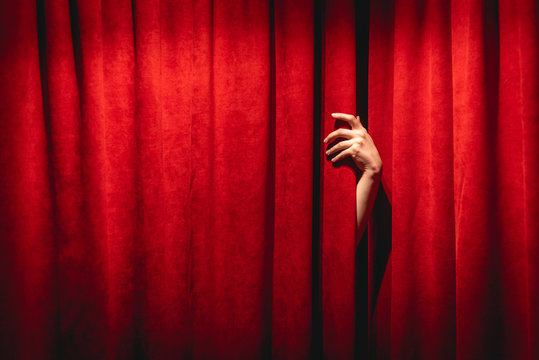 The hand on the red curtain background. The Twin peaks black lodge concept.