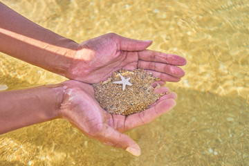 Hands of a woman holding Sand and a Starfish