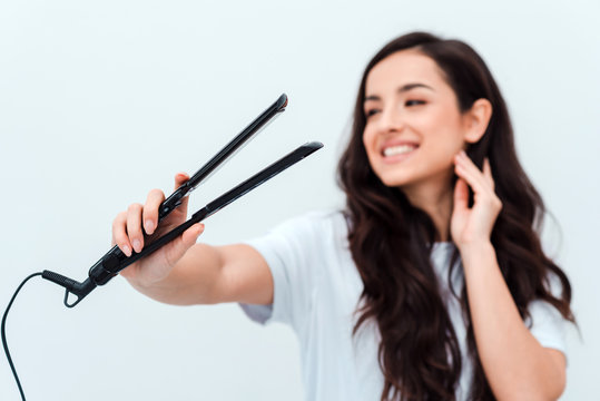 Pretty, smiling girl holding a straightener in her hands. Closeup, blurred background