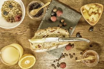 Petit déjeuner varié avec pain aux fruits secs et céréales jus d'orange frais miel salade de fruits et fruits rouges avec un bol de céréales et un couteau à beurre pour tartiner confiture
