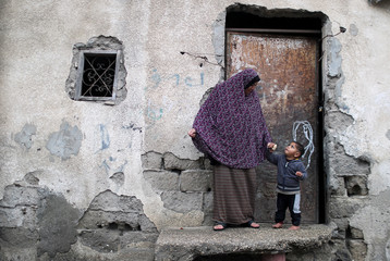 Palestinian woman holds the hand of her son outside their home on a rainy day in Beit Lahiya town in the northern Gaza Strip