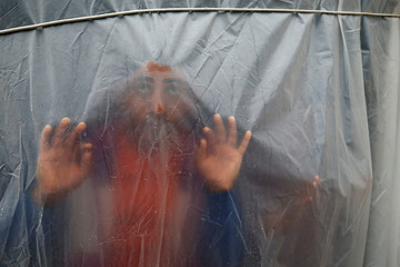 Palestinian man looks through a plastic sheet covering his house on a rainy day in Beit Lahiya town in the northern Gaza Strip