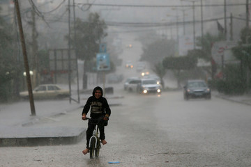Palestinian boy rides a bicycle on a street during a rainfall in Gaza
