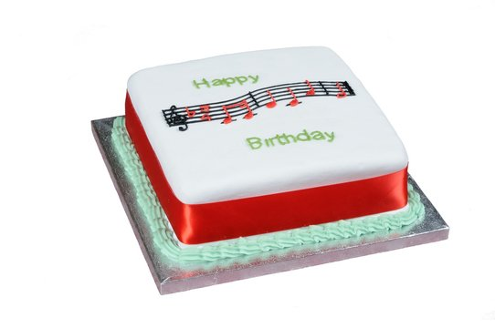 Happy Birthday music and text atop a square white cake.