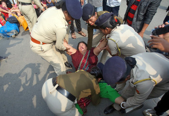 A demonstrator reacts as she is detained by police during a protest against the Citizenship Amendment Bill, in Agartala
