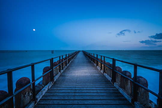 Long wooden pier extends over water toward the horizon. A leading line to the horizone