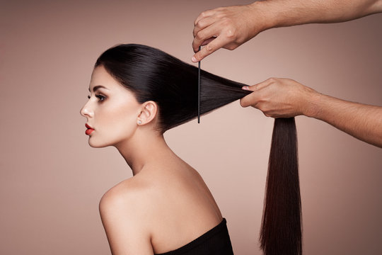 Hairdresser combs the hair of a woman. Portrait of beautiful young woman getting haircut. Care for long smooth hair