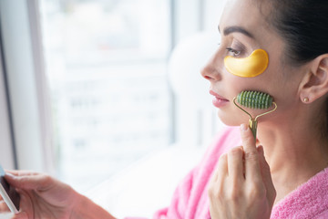 Woman with eye patches using jade massager stock photo