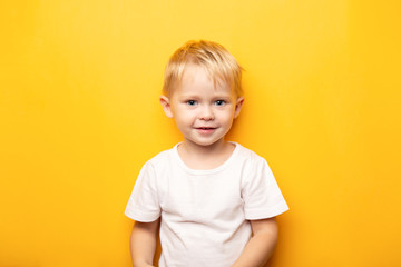2 years portrait of little blond happy caucasian blue eyes baby boy wearing on white t shirt on yellow background with copy space Fototapete