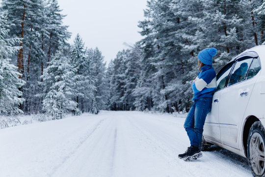 Side view of adult woman near car over snowy forest on winter roadtrip.