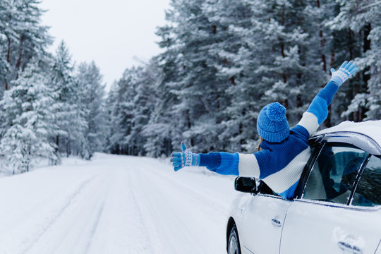 Rear view of adult woman in car over snowy forest on winter roadtrip.
