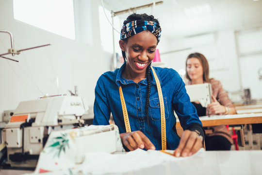 Young african textile worker sewing on production line.