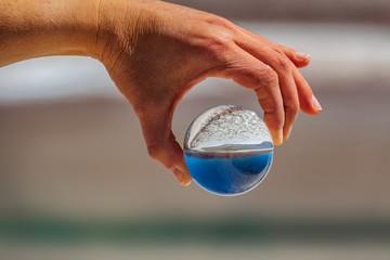 Hand holding glass ball over salt lake in Atacama