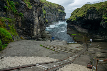 Gjogv gorge with tourist on the island of Eysturoy in the Faroe Islands.