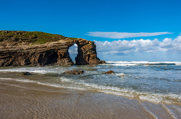 Cathedral beach iconic rocks with hole in Galicia
